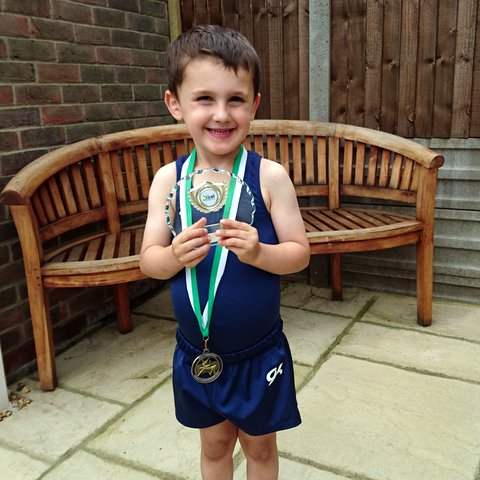 William with his xcel gymnastics medal and trophy.